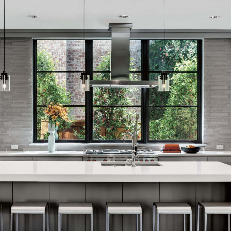 Open plan kitchen with island and stools, and black framed Marvin windows